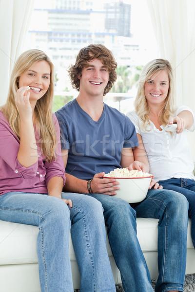 Drie vrienden eten popcorn glimlachend Stockfoto © wavebreak_media