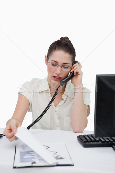 Portrait of a businesswoman making a phone call while looking at statistics against a white backgrou Stock photo © wavebreak_media