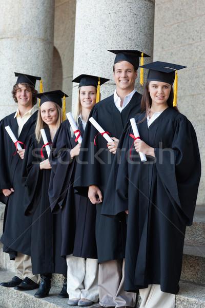 Happy smiling graduates posing in single line with columns in background Stock photo © wavebreak_media