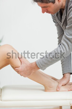 Serious osteopath holding the calf of a patient in a medical room Stock photo © wavebreak_media