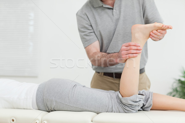 Woman lying forward while a physiotherapist examining her leg in a room Stock photo © wavebreak_media