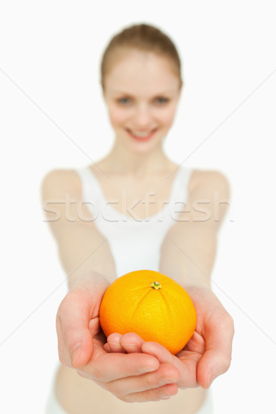 Close up of a woman presenting a tangerine against white background Stock photo © wavebreak_media