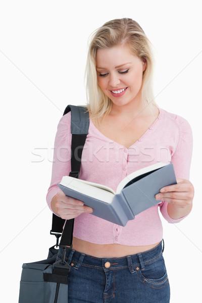 Smiling blonde woman reading a novel against a white background Stock photo © wavebreak_media