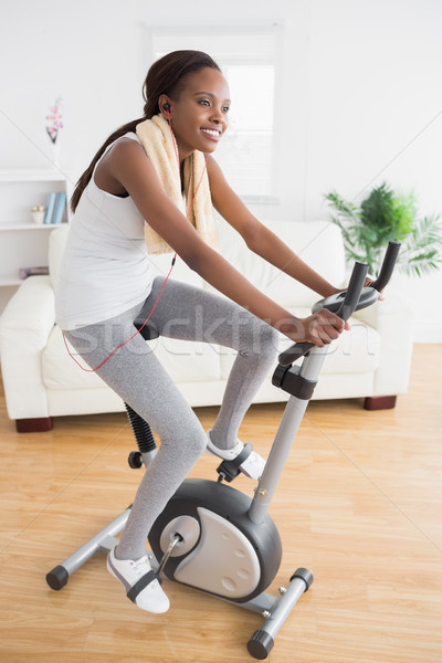 Black woman doing exercise bike while smiling in a living room Stock photo © wavebreak_media