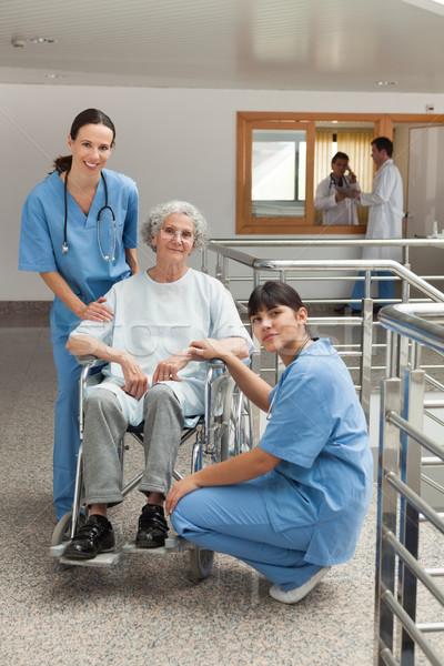 Two nursed with old woman in wheelchair in hospital corridor Stock photo © wavebreak_media