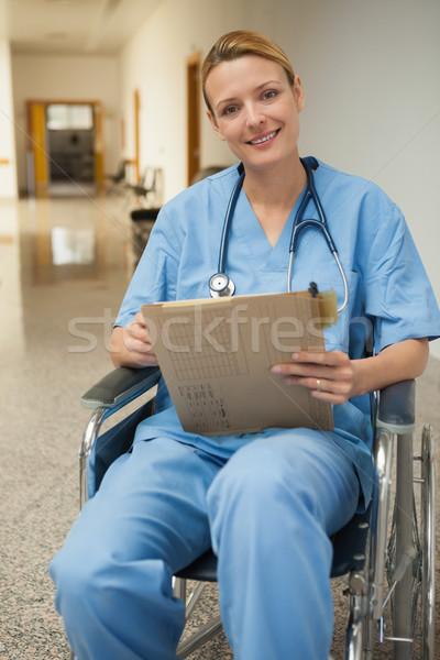 Uśmiechnięty pielęgniarki zauważa wózek szpitala korytarz Zdjęcia stock © wavebreak_media
