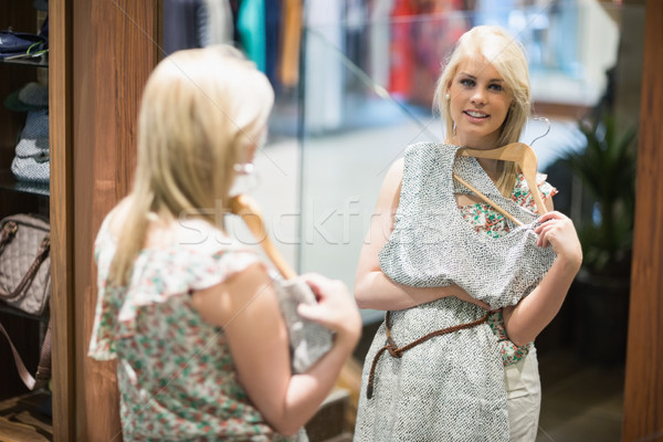 Woman is smiling in front of the mirror in the boutique Stock photo © wavebreak_media