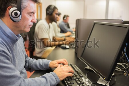 Man looking up from computer class in college Stock photo © wavebreak_media