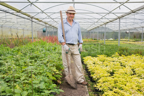 Man holding a spade while smiling and standing in the greenhouse Stock photo © wavebreak_media
