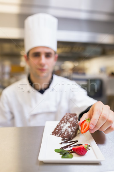 Chef putting a strawberry on dessert plate in the kitchen Stock photo © wavebreak_media