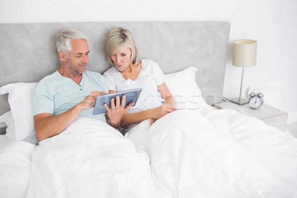 зрелый пару цифровой таблетка кровать счастливым Сток-фото © wavebreak_media