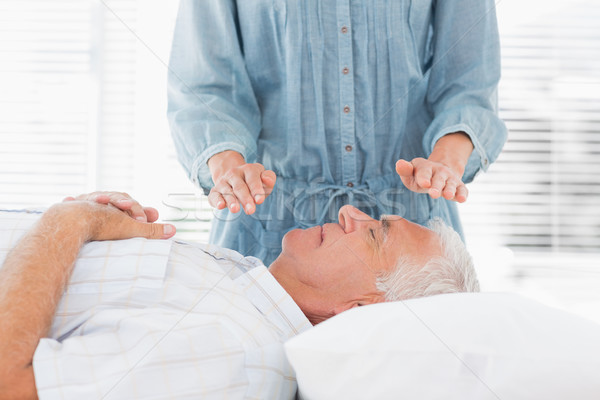Therapist performing Reiki over senior man Stock photo © wavebreak_media