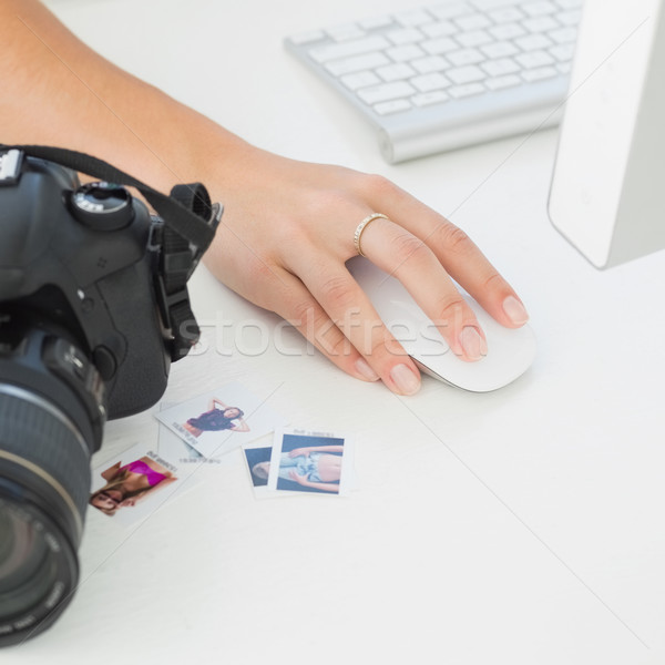 Digital camera on photographers desk with womans hand on mouse Stock photo © wavebreak_media
