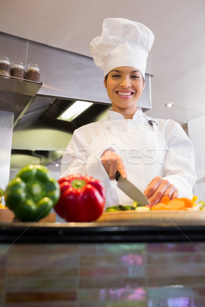 Stock photo: Smiling female chef cutting vegetables in kitchen