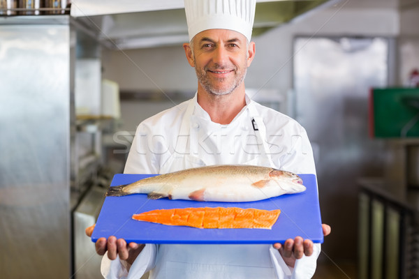 Confidence chef holding tray of raw fish in kitchen Stock photo © wavebreak_media