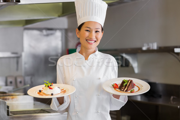 Confident female chef holding cooked food in kitchen Stock photo © wavebreak_media