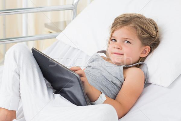 Sick girl with digital tablet in hospital bed Stock photo © wavebreak_media