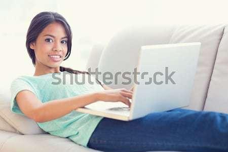 Pretty girl lying on sofa using her laptop smiling at camera Stock photo © wavebreak_media