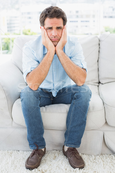 Upset man sitting on the couch looking at camera Stock photo © wavebreak_media