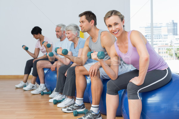 Class with dumbbells sitting on exercise balls in gym Stock photo © wavebreak_media