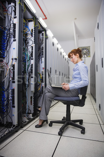 Technician sitting on swivel chair using laptop to diagnose serv Stock photo © wavebreak_media