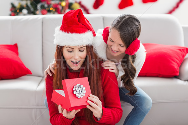 Festive mother and daughter with a christmas gift Stock photo © wavebreak_media