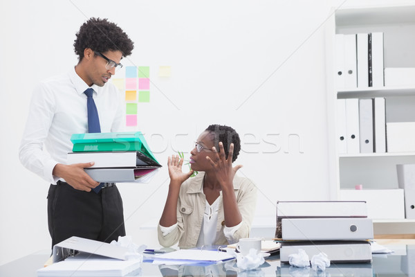 Man giving pile of files to his irritated colleague Stock photo © wavebreak_media
