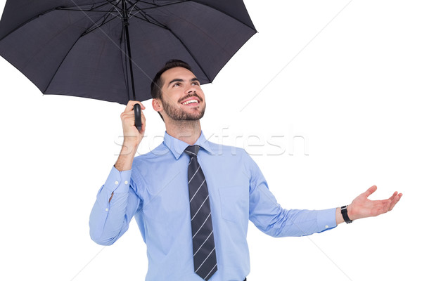 Happy businessman sheltering with a black umbrella Stock photo © wavebreak_media
