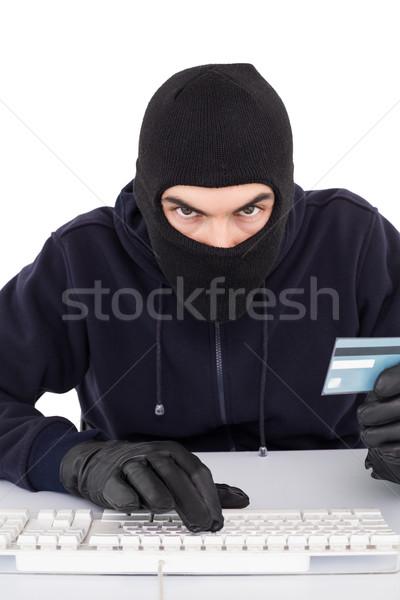 Concentrated burglar in balaclava shopping online Stock photo © wavebreak_media