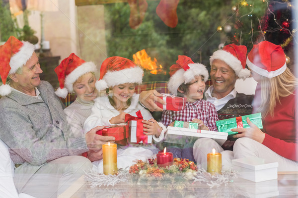 Stock photo: Multi generation family holding a lot of presents on sofa