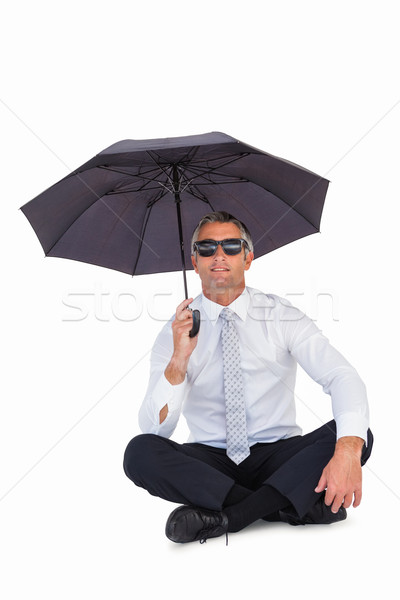 Businessman wearing sunglasses and sheltering with umbrella Stock photo © wavebreak_media