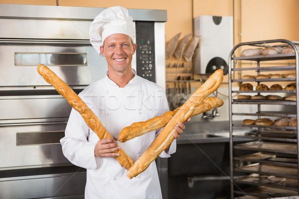 Sorridente padeiro três baguettes cozinha Foto stock © wavebreak_media