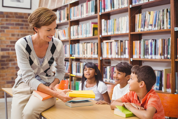 Cute pupils and teacher looking for books in library Stock photo © wavebreak_media