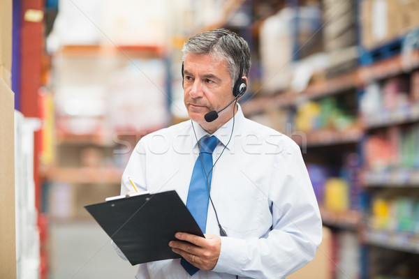 Warehouse manager wearing headset writing on clipboard Stock photo © wavebreak_media
