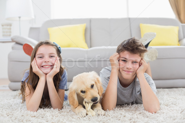 Happy siblings with puppy lying on rug Stock photo © wavebreak_media
