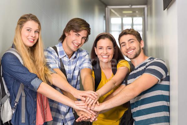 College students placing hands together Stock photo © wavebreak_media