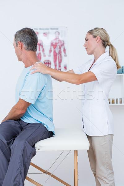 Doctor examining her patient neck Stock photo © wavebreak_media
