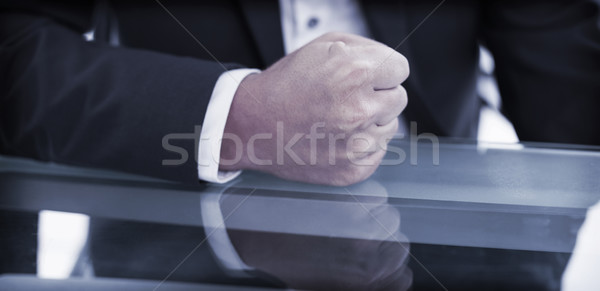 Mid section of businessman with clenched fist on office desk Stock photo © wavebreak_media