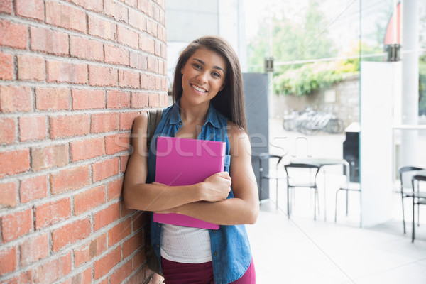 Pretty student smiling and holding notepads Stock photo © wavebreak_media