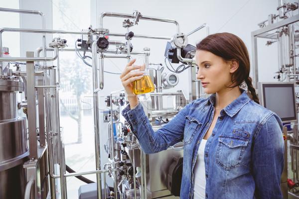 Stylish brunette in denim jacket looking at beaker of beer Stock photo © wavebreak_media