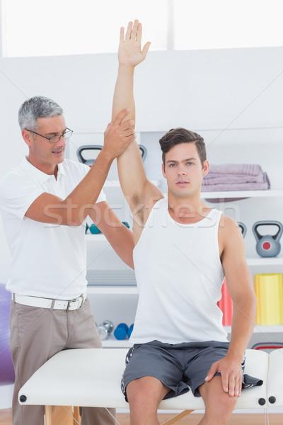 Doctor raising a young man arm Stock photo © wavebreak_media