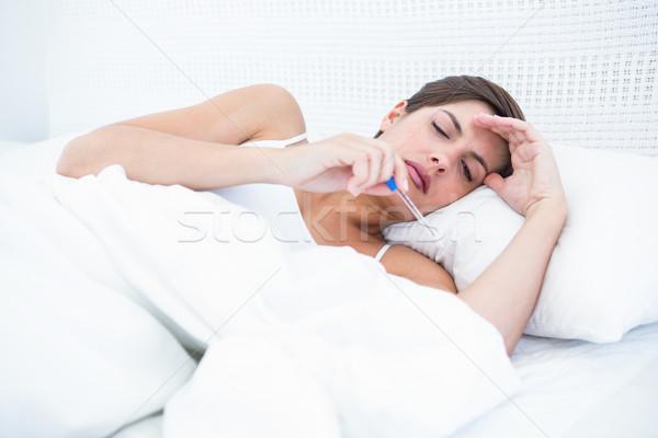 больным женщину глядя термометра домой спальня Сток-фото © wavebreak_media