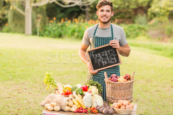 Handsome farmer standing at his stall and holding chalkboard  Stock photo © wavebreak_media