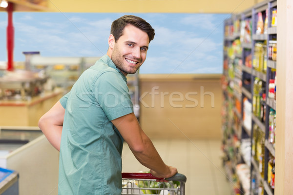 Portrait of smiling man pushing his trolley in aisle  Stock photo © wavebreak_media