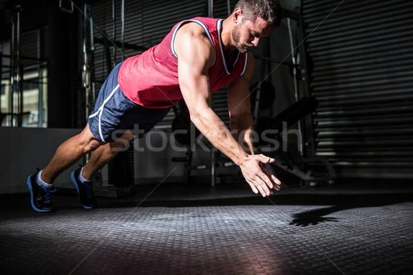 Stock photo: Muscular man doing push-ups with hand clapping