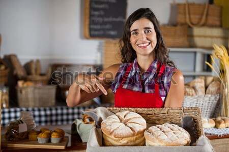 Smiling waitress picking up bread from a basket Stock photo © wavebreak_media