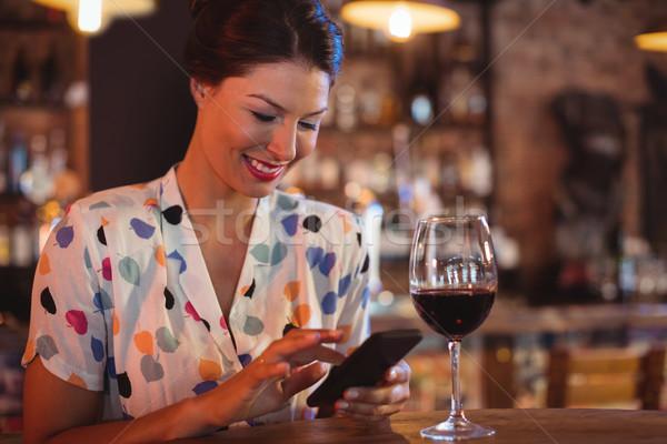 Young woman using mobile phone while having wine Stock photo © wavebreak_media