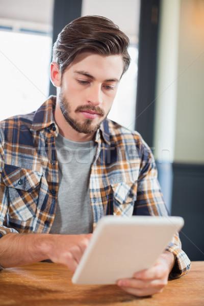 Handsome young man using digital tablet Stock photo © wavebreak_media