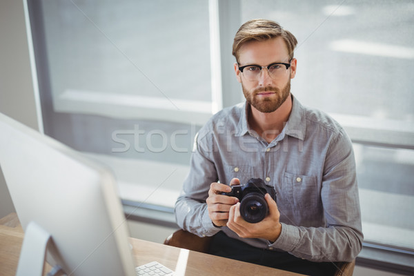 Portrait of confident executive holding digital camera at desk Stock photo © wavebreak_media