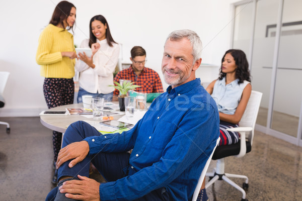 Portrait of smiling businessman with colleagues in background Stock photo © wavebreak_media